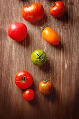 Colorful ripe tomatoes. Delicious vegetarian food. Dark backgrou