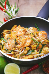 Famous traditional thai food shrimp pad thai, rice noodle stir-fry with prawns, tofu and vegetables on cooking pan.
