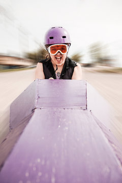 Young girl screaming as she's rolling down a hill in a soapbox car
