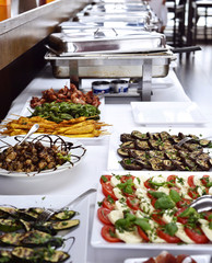 Party buffet with italian Antipasti and metal containers with cooked food.