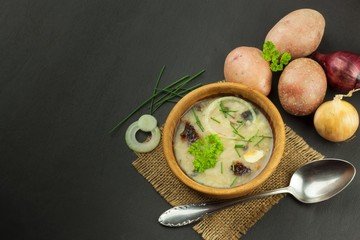 Homemade potato soup with mushrooms. Bowl with potato soup on wooden table. Food preparation.