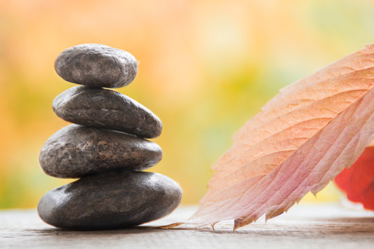 Stones spa with autumn leaves on the blurred background. Zen like concepts.