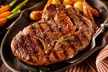 Serving of marinated rib eye steak with potatoes