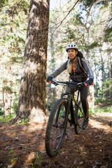 Female mountain biker riding bicycle in the forest