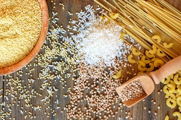 Gluten free cereals corn, rice, buckwheat, quinoa, millet and pasta and flour on brown wooden background
