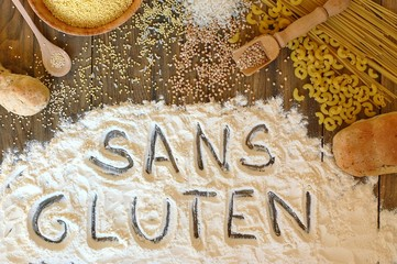 Gluten free cereals corn, rice, buckwheat, quinoa, millet, pasta and flour with text gluten free in French language on brown wooden background