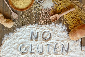 Wall Mural - Gluten free cereals corn, rice, buckwheat, quinoa, millet, pasta and flour with scratched text no gluten on brown wooden background