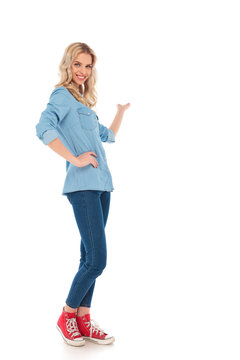 full body picture of a smiling young casual woman presenting