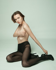 seductive woman sitting in fashion pose wearing black pantyhose
