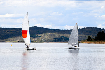 Two sail boats during a local race on a lake at the foothills of a mountain range
