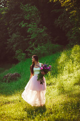 charming girl admires a beautiful green meadow