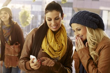 Girls looking at photos on mobilephone