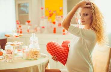 Charming pregnant woman holding a heart