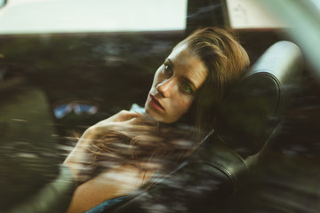 Brunette in the back seat of car, tinted photo