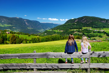Two adorables little sisters admiring beautiful landscape of Dolomites mountain range, South Tyrol, Italy
