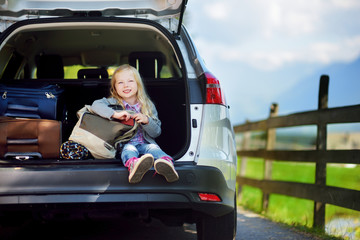 Adorable little sitting in a car before going on vacations with her parents.