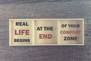 Real life begins at the end of your comfort zone. Inspirational quote written on wooden box