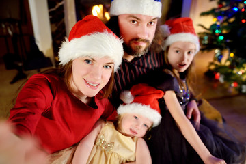 Young happy family of four taking a photo of themselves on Christmas