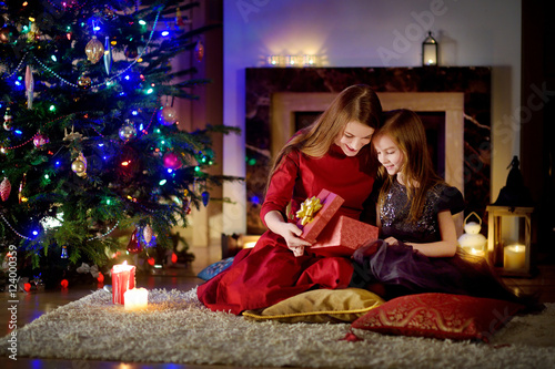 Young mother and her daughter unwrapping Christmas gifts by a ...