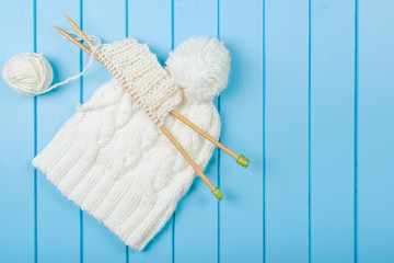 Knitted white scarf and hat on blue wooden background.