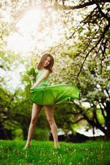 beautiful young woman jumping in a green garden