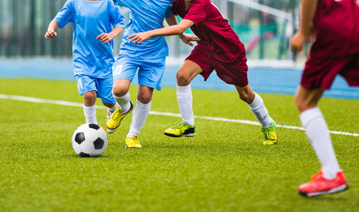 Young soccer players running towards soccer ball. Football soccer game for youth teams. Children playing soccer match