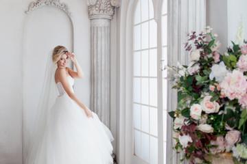 Charming young bride in luxurious wedding dress. Pretty girl, is near big window