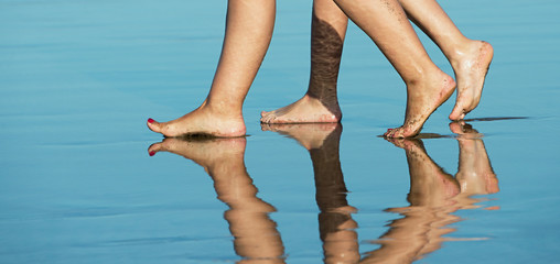 Womans legs while walking on the beach of reflection in the water