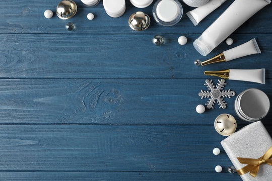 Beauty cosmetic products with Christmas decoration and gift on blue wooden background