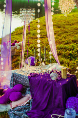 Table decorated with violet cloth and pillows stands on the gree