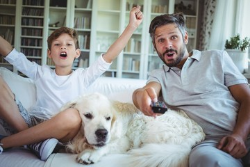 Father and son sitting on sofa with pet dog