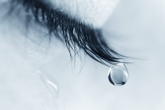 Sad woman concept - closed eyelid closeup with a teardrop on eyelashes.  A tear on eyelashes macro close-up. A tear runs down his cheek. Tinted blue.