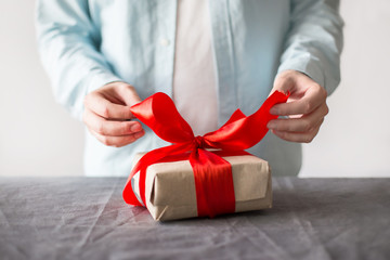 Man opening present with craft paper box and red ribbon