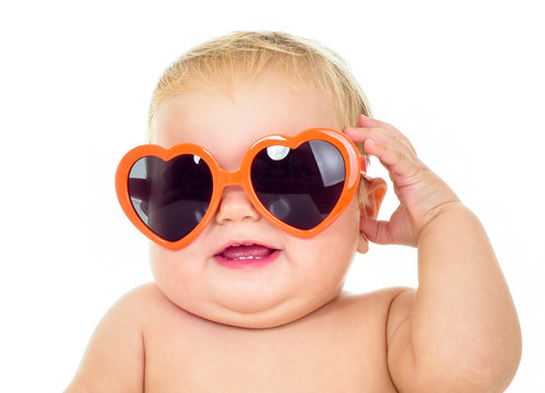 Beautiful smiling baby in sunglasses. One, isolated on white.