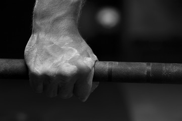 Closeup of male hand holding barbell