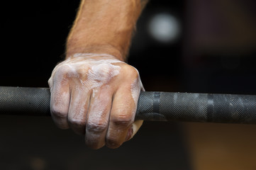 Male hand with powder holding barbell