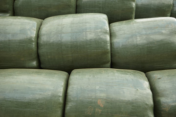 A whole page of green farm hay bails background texture