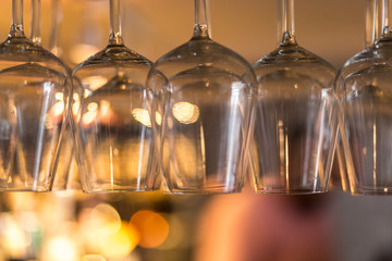 detail of different sized wine glasses hanging from a bar rack. space for lettering, copy and text.