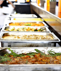 Party buffet with metal containers filled with cooked food.