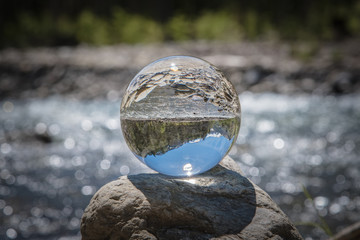 Wildbach spiegelt sich in einer Glaskugel