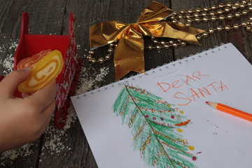 child writes letter to Santa and draw a Christmas tree. Golden Christmas beads and gold ribbon bows on wooden background.