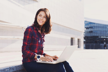 Beautiful young woman using laptop outdoors