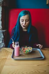Nerd teen in beanery eating.