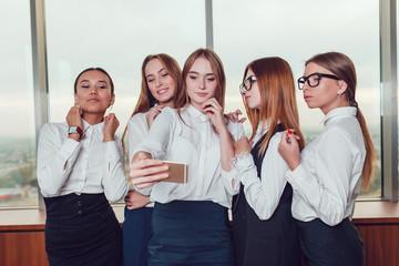 Five business women make selfie against the window