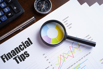 "Magnifying glass on colourful pie chart with ""Financial tips"" text on paper, dice, spectacles, pen, laptop calculator on wooden table - business, banking, finance and investment concept"