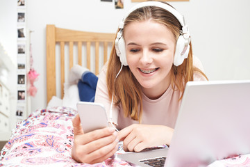 Teenage Girl Listening To Music Whilst Using Mobile Phone
