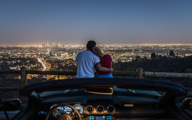 Couple enjoying skyline view from their car
