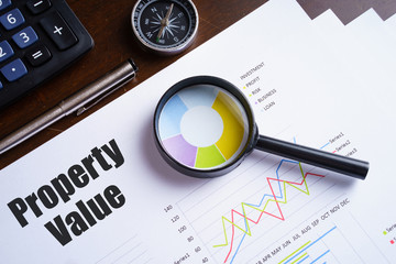 """Property Value"" text on paper sheet with magnifying glass on chart, dice, spectacles, pen, laptop and blue and yellow push pin on wooden table - business, banking, finance and investment concept"