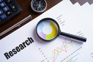 "Magnifying glass on ""Research"" text on chart, dice, spectacles, pen, laptop calculator on wooden table - business, banking, finance and investment concept"