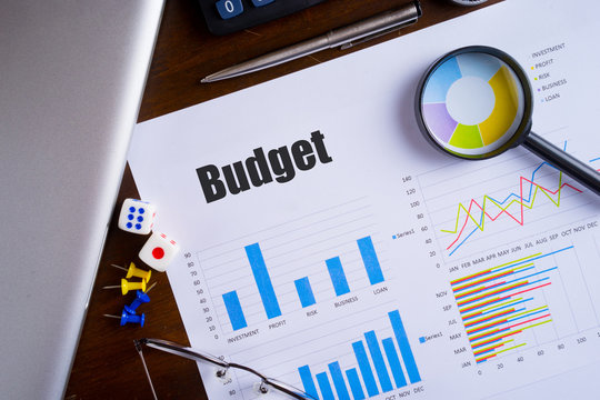 """""""Budget"""" text on paper sheet with magnifying glass on chart, dice, spectacles, pen, laptop and blue and yellow push pin on wooden table - business, banking, finance and investment concept"""